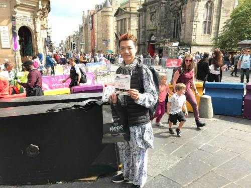 Behind the Mirror cast member promoting the show on the Royal Mile