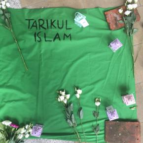 A green banner on the floor, with the name Tarikul Islam painted in black. White flowers are placed at the edge of the banner.