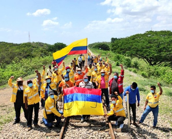 The railway line which supplies the Cerrejón coal mine, blockaded by former workers. They carry a Colombian flag with SOS written on it.