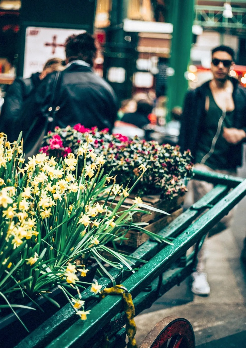 Other London Markets - Man walking past flower stand