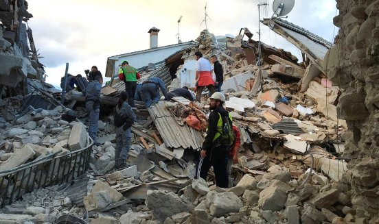 Rescuers work at a collapsed house following a quake in Amatrice, central Italy, August 24, 2016. REUTERS/Emiliano Grillotti