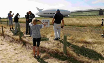 People look through the perimeter fence at the Airlander 10 hybrid airship following a crash-landing during a test flight at Cardington Airfield in Britain, August 24, 2016. REUTERS/Darren Staples