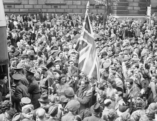 A young man holds aloft a large Union Flag amongst the huge crowd of people that has gathered in Whitehall