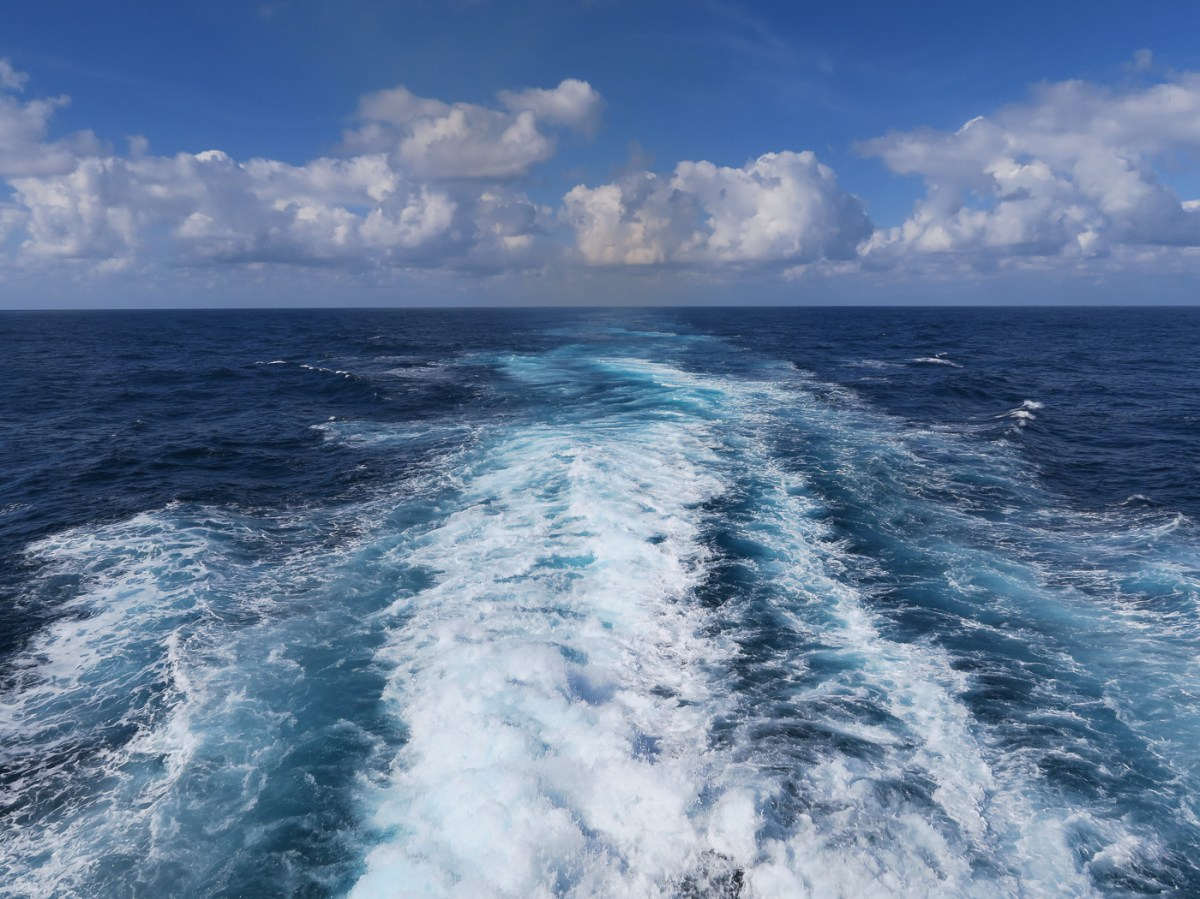 Blue sea and sky and the wake of a boat in the waves
