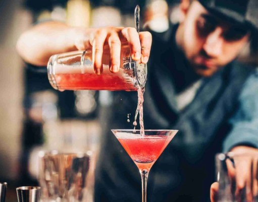 barman preparing and pouring red cocktail in martini class.