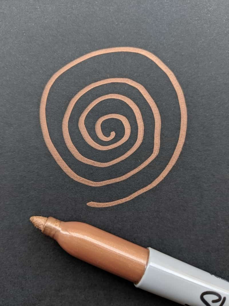 Image of a spiral drawn on black paper as an art therapy idea