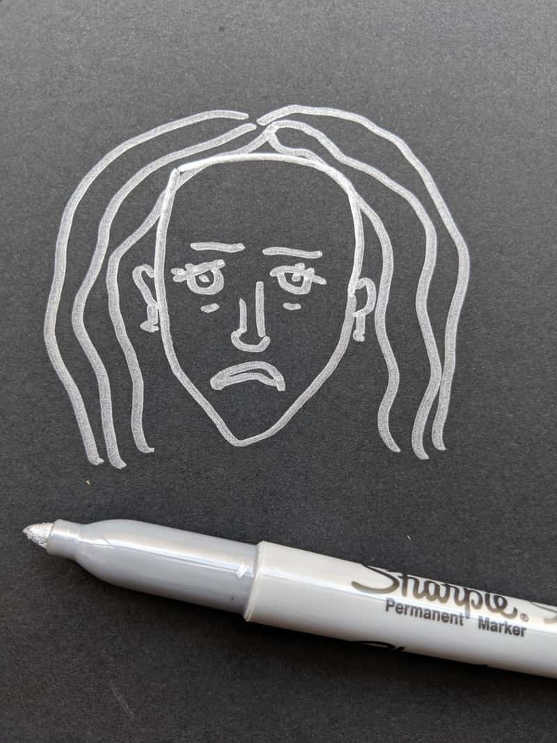 Image of a sad face drawn on paper as an art therapy idea