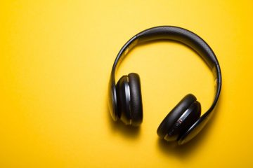 A pair of black headphones against a solid yellow background