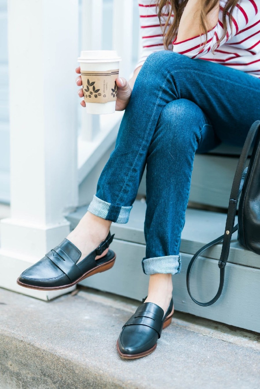 Wearing a pair of Kelsi Brooklyn Dagger black slip on loafers from Anthropologie with cuffed blue jeans.