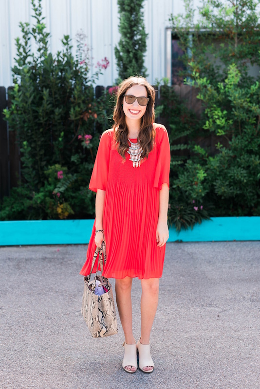 Styling a red anthropologie pleated shift dress with snake print shoes and a matching tote.