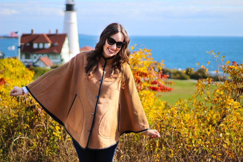 New England outfit inspiration with a J. McLaughlin poncho at Portland Head Light in Maine.