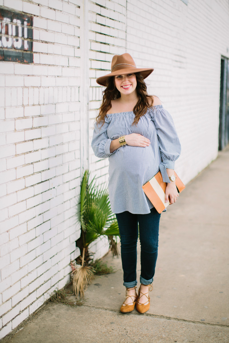 Houston fashion blogger styles a striped off the shoulder maternity top with maternity jeans, vionic lace up flats and a striped clare vivier clutch.
