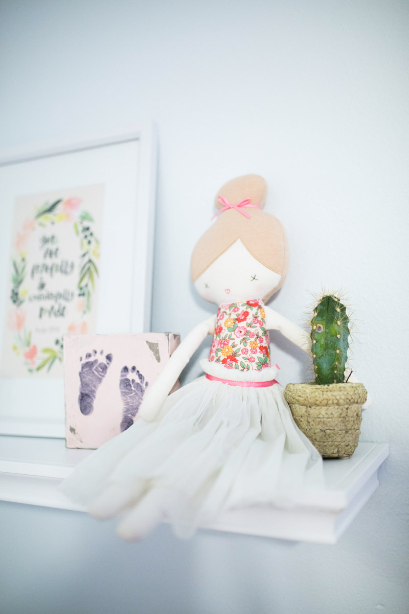 Baby girl nursery floating shelf with Anthropologie doll & succulent.