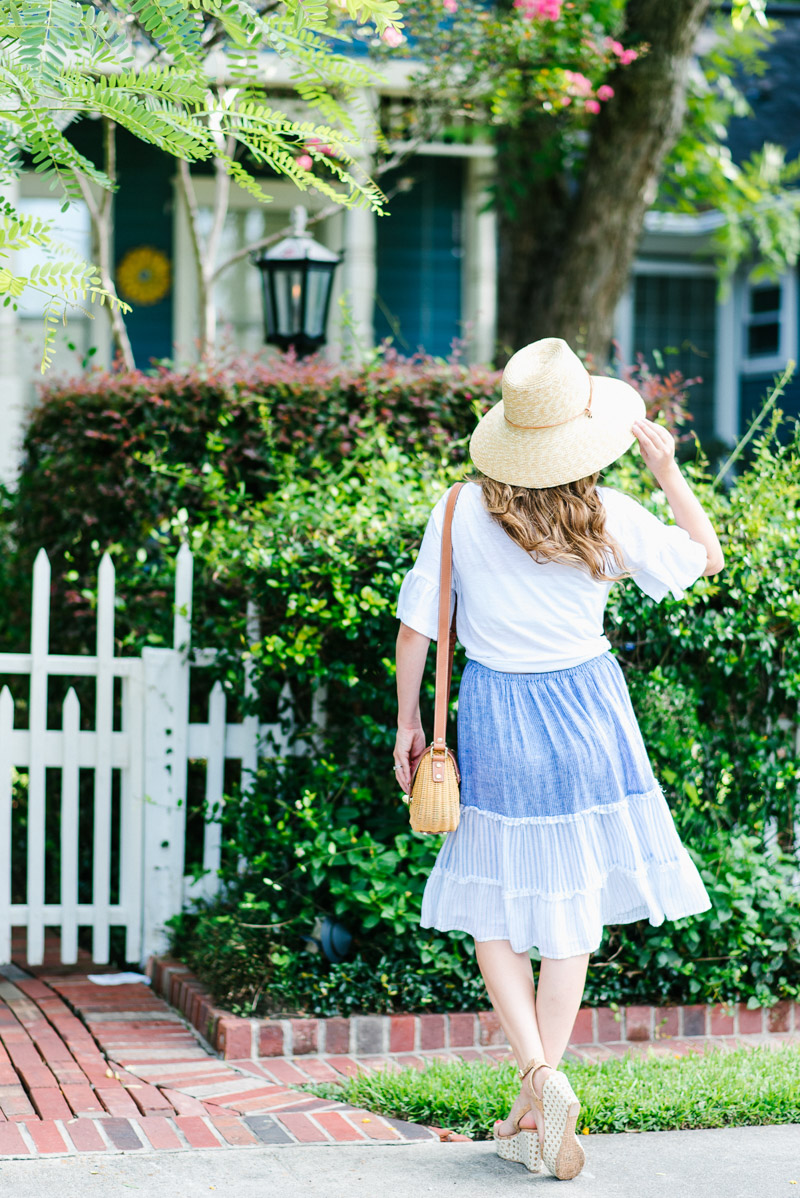 Anthropologie blue and white striped skirt paired with a white top and a straw sun hat.