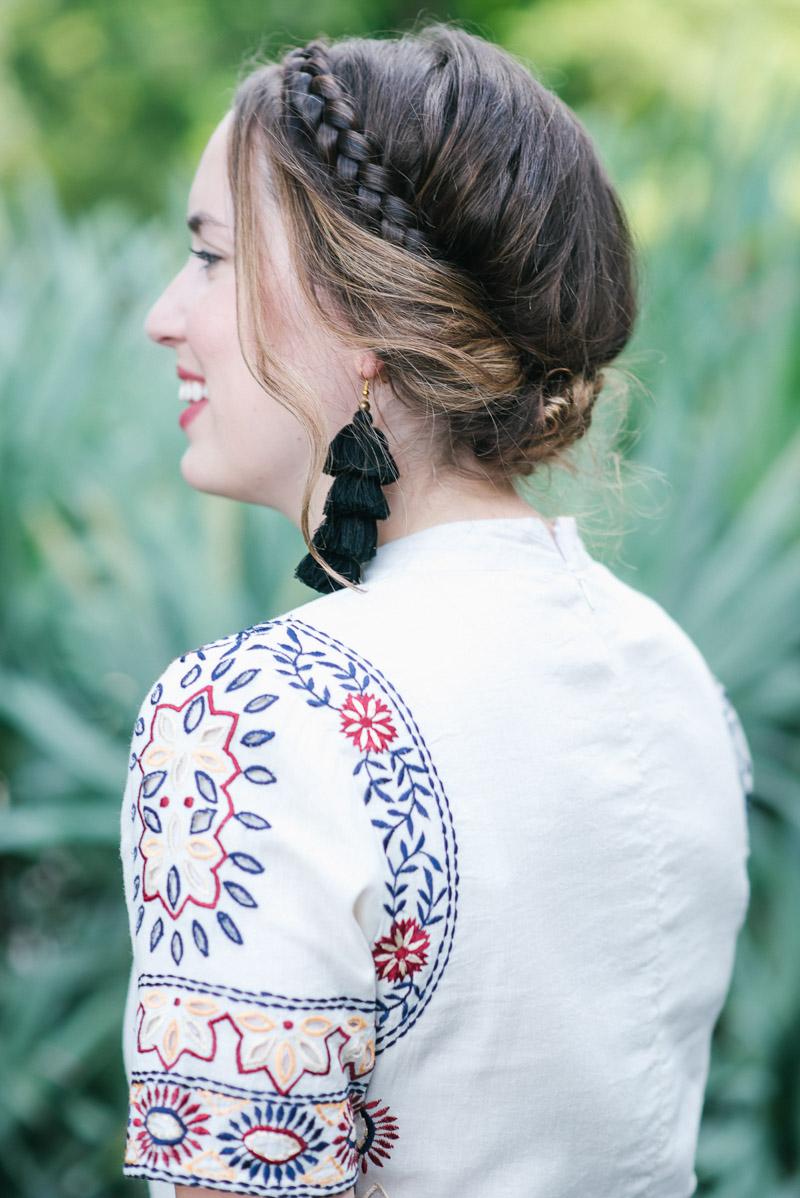 Texas fashion blogger styles a boho crown braid hairstyle with black tassel earrings.