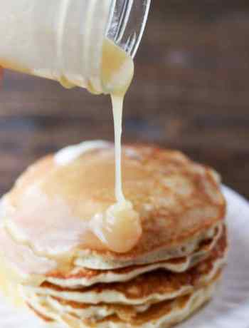 Pouring homemade syrup on a stack of pancakes.