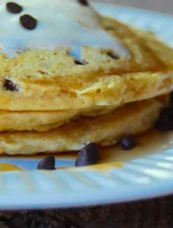 Stack of three chocolate chip pancakes made from chocolate chip pancake mix topped with whipped cream, side view.
