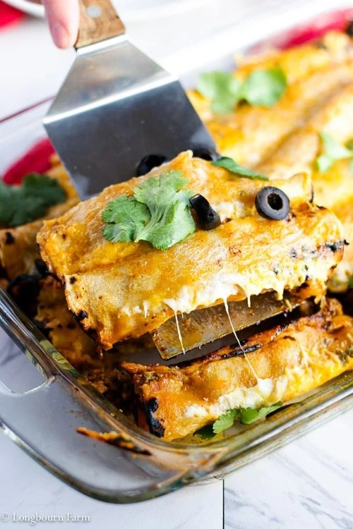 Lifting cheesy beef enchiladas out of a pan.