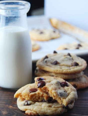 Broken homemade chocolate chip cookie in front of a glass of milk and more chocolate chip cookies.