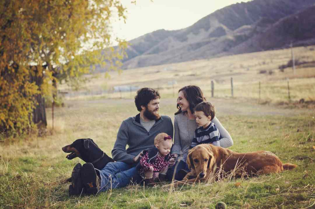 Alli, Andy, kids, and dogs sitting on their property.
