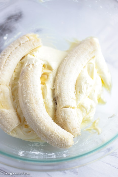 Ripe bananas in a bowl over creamed butter, sugar and eggs for chocolate chip banana recipe.