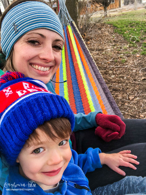 Mommy and Abram sitting in the hammock.