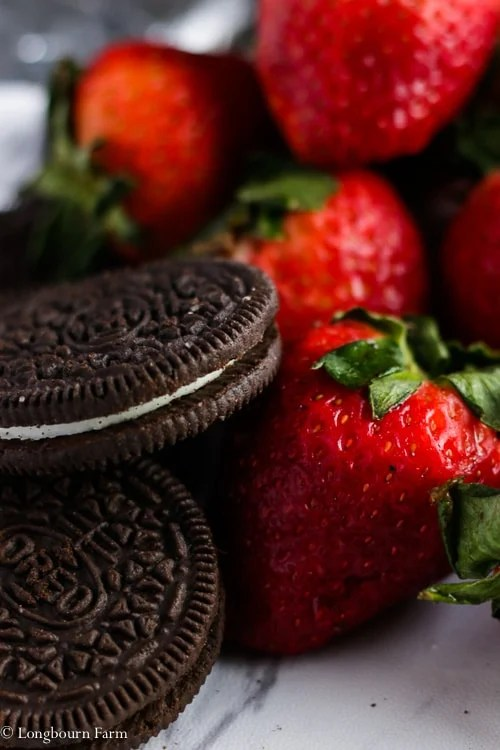 Oreos next to a pile of strawberries.