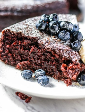 Closeup, side view, of a slice of basic chocolate cake topped with blueberries.