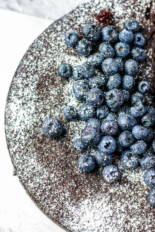 Top view of basic chocolate cake recipe topped with blueberries.