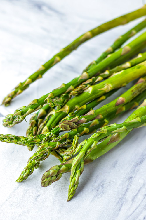 Pile of asparagus spears on a tile marble counter.
