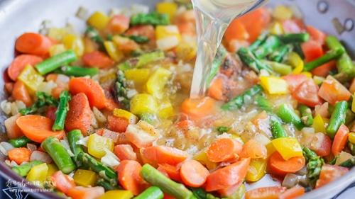 Pouring chicken broth into the veggies for pasta primavera recipe.