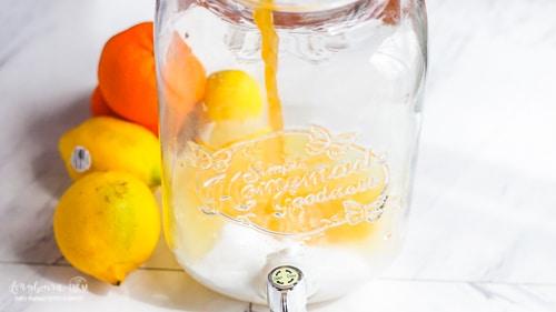 Pouring orange juice into mixing vat for citrus lemonade.