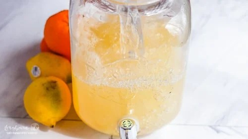 Adding water to citrus lemonade to finish making the recipe.