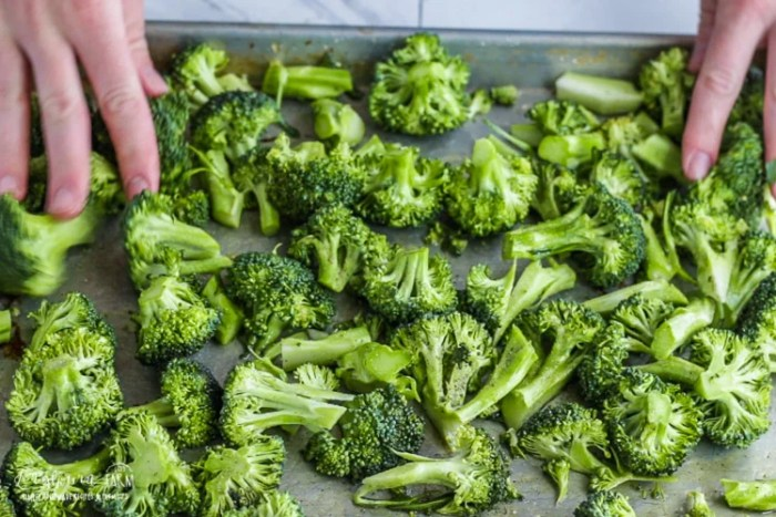 Spreading oven roasted broccoli into a single layer.