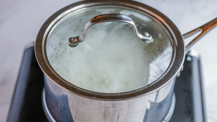 Water simmering in a covered pot cooking the white rice recipe.