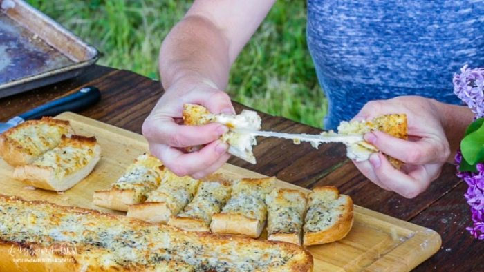 Breaking and pulling apart a slice of cheesy garlic bread.
