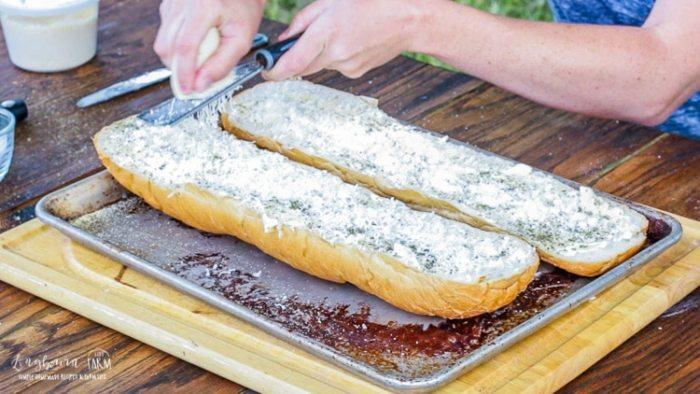 Grating mozzarella cheese on halves of french bread for cheesy garlic bread.