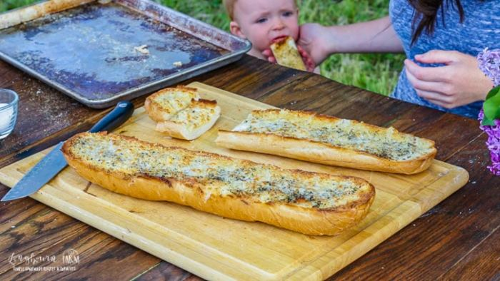Cute baby sneaking some cheesy garlic bread from the cutting board.