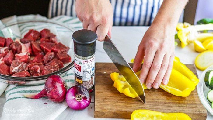 Chopping yellow pepper for steak kabobs.