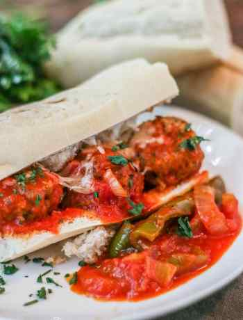 Meatball sub on a white plate.