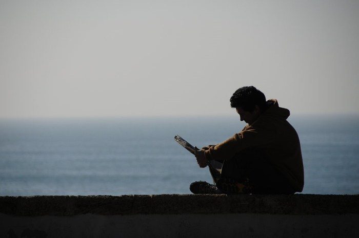 """""""Silhouette of a man reading by the ocean"""" (Kamil Porembiński/Creative Commons)"""