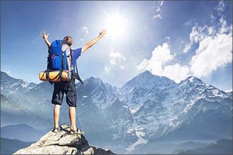 Mann steht auf einem Berg und streckt die Hände Richtung Sonne