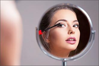 Frau schminkt sich in Schminkspiegel
