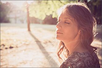 Frau badet mit geschlossenen Augen im Licht