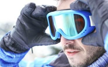 Mann setzt sich eine Skibrille auf