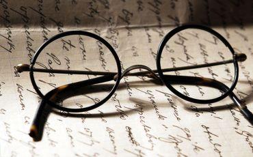Alte Brille liegt auf altem Schriftstück