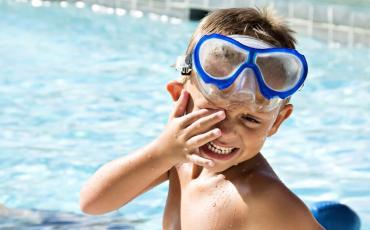 Junge im Schwimmbad reibt sich die Augen