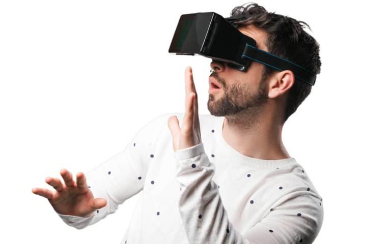 Mann trägt VR-Brille und ist begeistert.