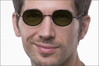 Mann trägt runde Sonnenbrillle mit grünen Gläsern