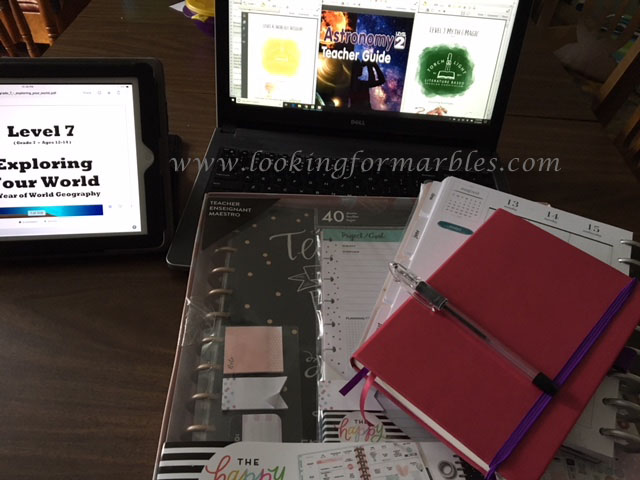picture of computer and ipad with pdfs open, bullet journal, classic Happy Planner and teacher Happy Planner still in the box